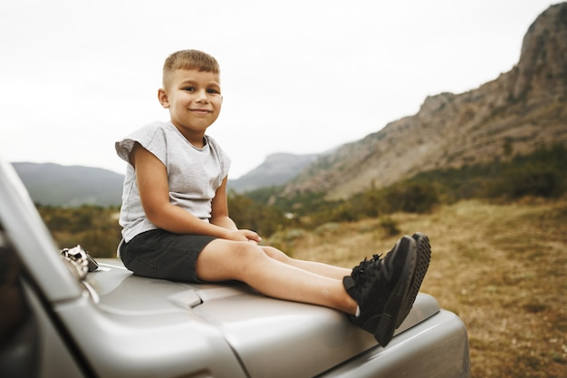 Little boy sitting on a hood of an offroad car parked in mountains