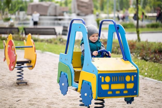 Маленький мальчик сидит в деревянной машине на детской площадке