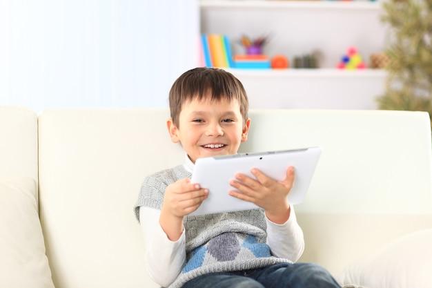 Маленький мальчик сидит на диване с электронным планшетом