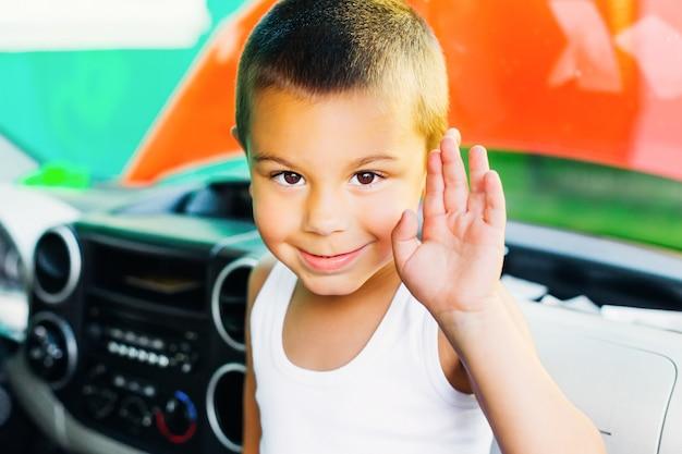 Маленький мальчик сидит в машине и улыбается и машет рукой