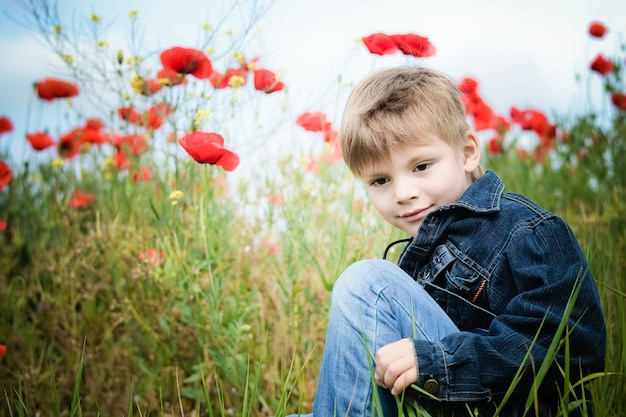 Little boy sitting in a meadow on a background of red poppies