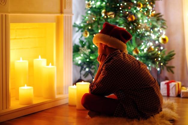 部屋の暖炉のそばに座っている小さな男の子