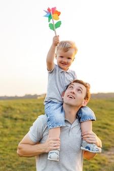 Маленький мальчик сидит на плечах папы и играет с красочной ветряной мельницей отец и сын веселятся Premium Фотографии
