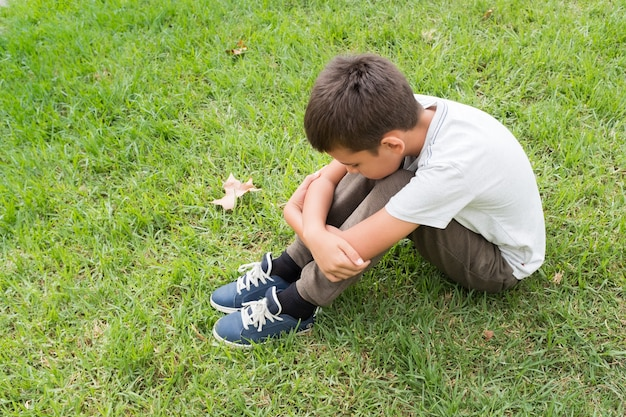 Маленький мальчик сидит на траве