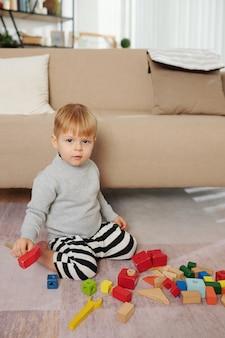 바닥에 앉아서 방에서 다채로운 블록을 가지고 노는 어린 소년