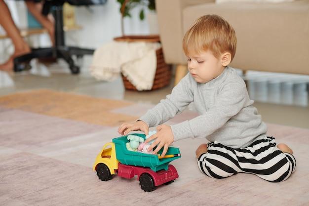 바닥에 앉아서 방에서 장난감 자동차를 가지고 노는 어린 소년