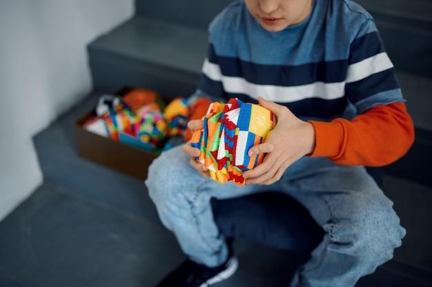 계단에 앉아 퍼즐 큐브를 가지고 노는 어린 소년. 두뇌 및 논리적 마인드 훈련, 창의적인 게임, 복잡한 문제 해결을 위한 장난감