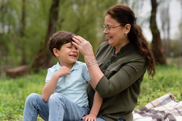Little boy sitting in the park with his grandmother