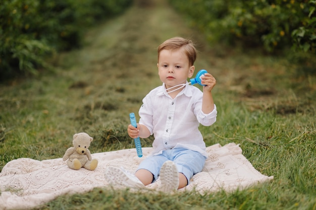 Little boy sitting on picnic plaid in cottage garden
