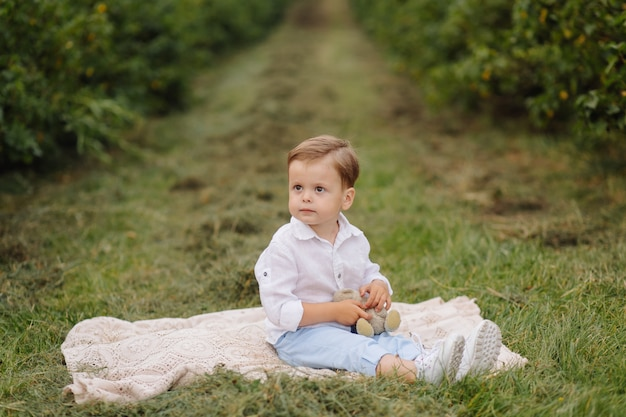 Little boy sitting on picnic plaid in cottage garden