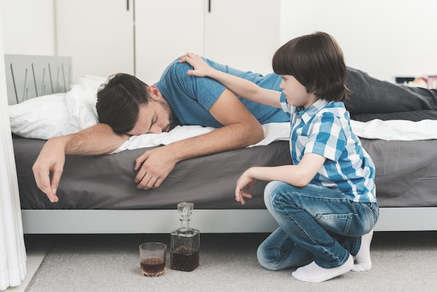 Little boy sitting in room with drunken father.