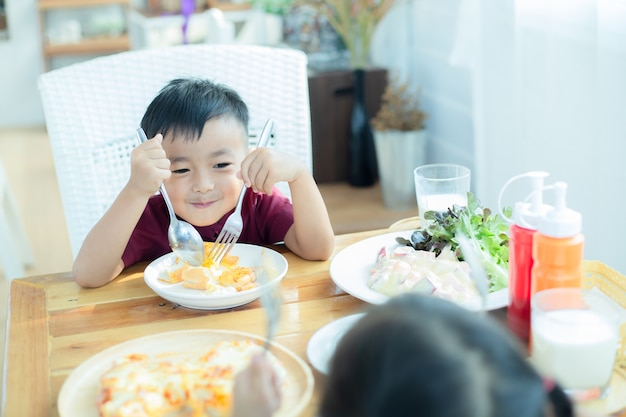 Little boy sitting at the table, eating breakfast