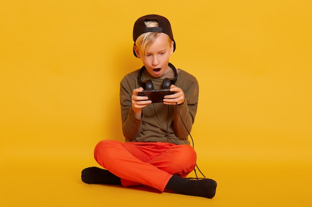 Little boy sitting with smartphone in, guy wearing casually with headphones around neck, posing withopened mouth and looks excited, child with crossed legs, holding mobile phone in hands.