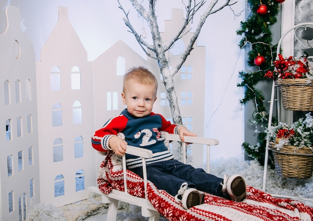 Little boy sitting in the wooden decorated sled, in winter interior. concept of merry christmas and new year