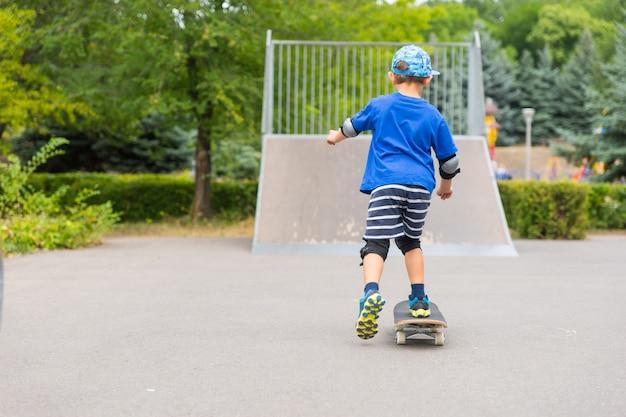 新鮮な空気の中で暑い夏の日を楽しんでいる彼のスケートボードのスケートパークでランプに向かってスケートをしている小さな男の子