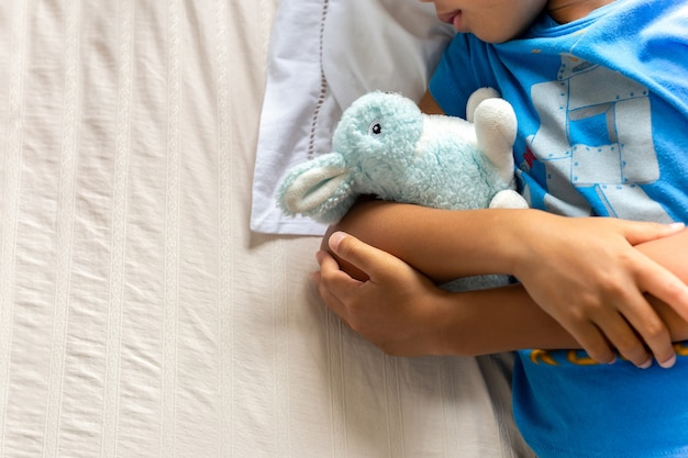 Little boy sleeping in bed holding his bunny robbit