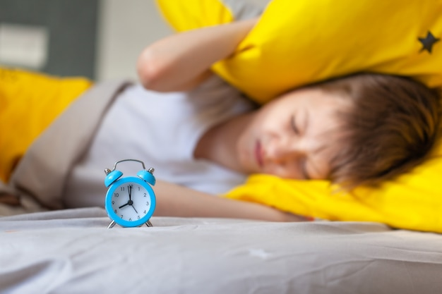 Little boy sleeping in bed with an alarm clock near his head