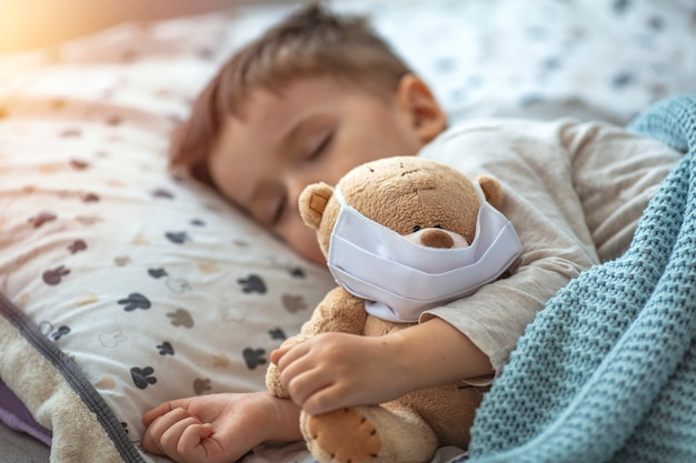 Little boy sleeping in his bed with his teddy bear wearing a mask to protect him against corona virus covid-19 / 2019-ncov concept.