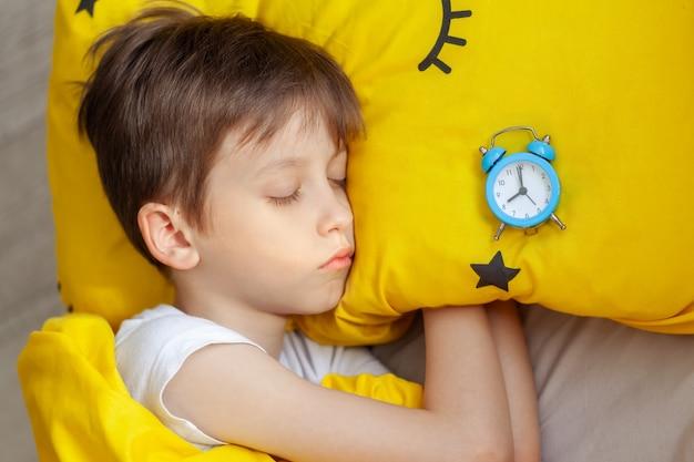 Маленький мальчик спит в постели с будильником возле головы