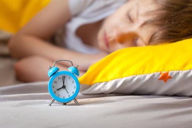 彼の頭の近くの目覚まし時計でベッドで寝ている少年
