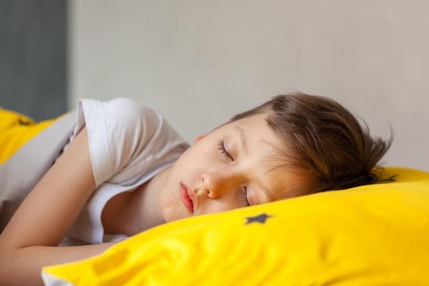 黄色いベッドで寝ている少年。健康的な睡眠の概念。