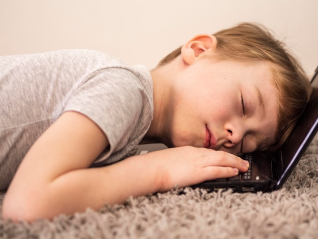 Маленький мальчик спит на клавиатуре своего ноутбука