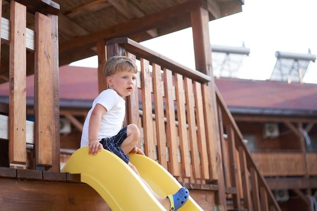 小さな男の子のスライド遊び場アクティブな子供時代夏を楽しむ白人の子供は屋外で楽しんでいます。夏休み