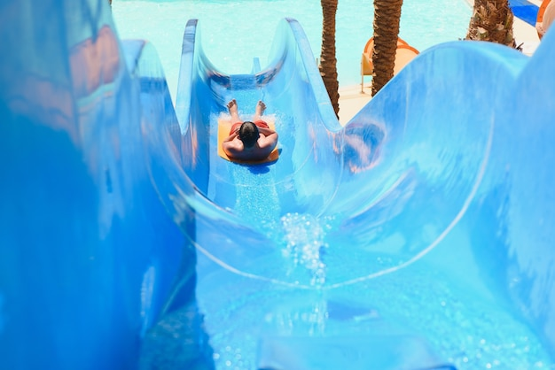 Little boy sliding on the water slides at the water park close up