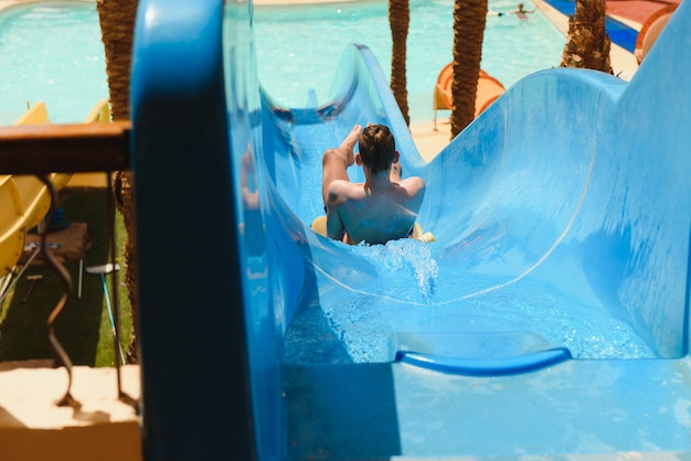 Little boy sliding on the water slides at the water park