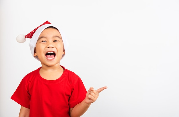 Little boy smile and excited in red santa claus hat point finger to side away the concept of holiday xmas day