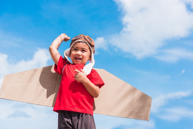 Little boy smile wear pilot hat and goggles play toy cardboard airplane wing flying raises hand up against summer