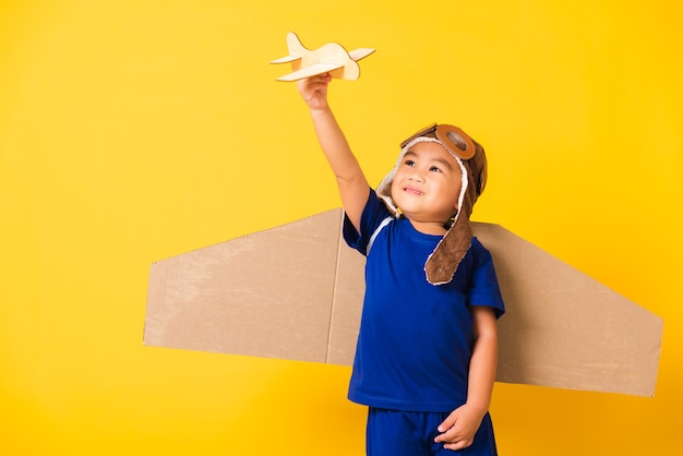 Little boy smile wear pilot hat play and goggles with toy cardboard airplane wings fly