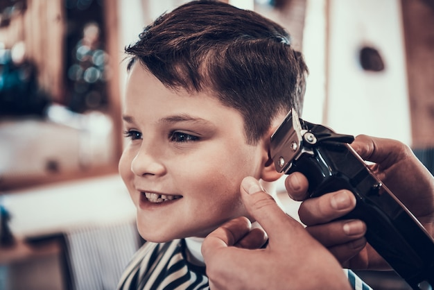 The little boy smiles when his hair is cut.