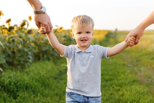 Маленький мальчик улыбается и держится за руки родителей на фоне сельской местности малыш с семьей