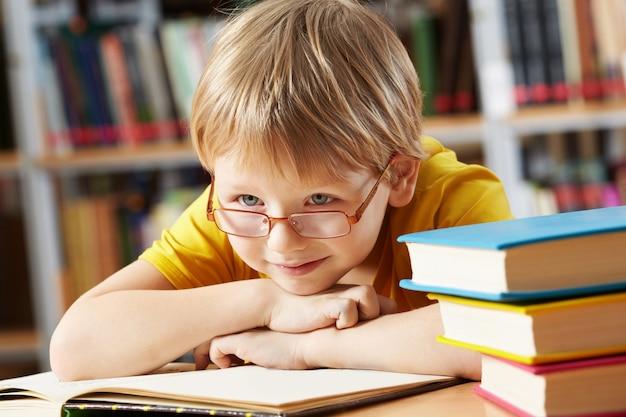 Маленький мальчик, улыбаясь в библиотеке