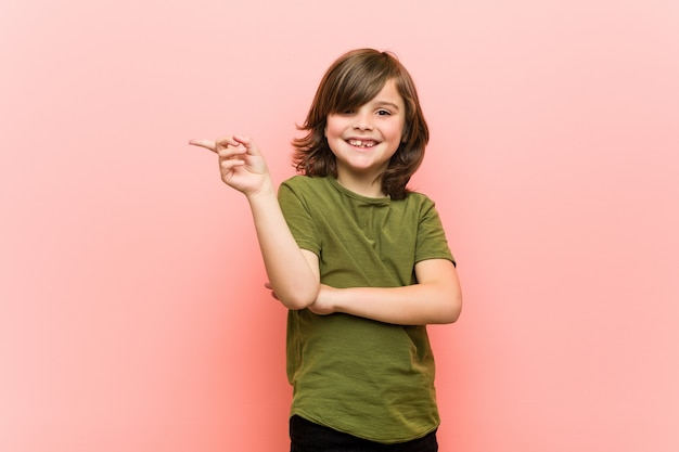 Little boy smiling cheerfully pointing with forefinger away.