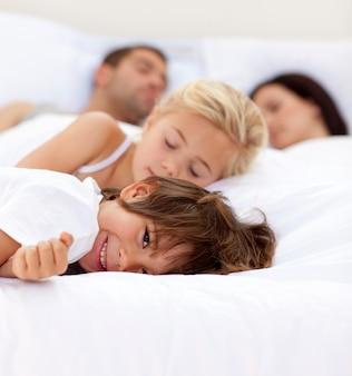彼の家族が眠るベッドの上に笑っている小さな男の子
