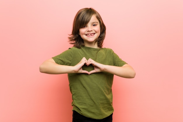 Little boy smiling and showing a heart shape with hands.