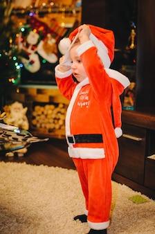 小さな男の子はサンタクロースの衣装でクリスマスツリーの近くに立っています