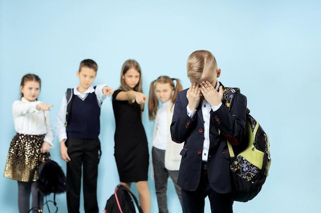 혼자 서서 아이들이 조롱하는 동안 괴롭힘을당하는 어린 소년
