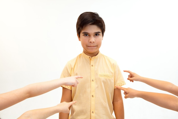 Little boy standing alone and suffering an act of bullying while children mocking in the wall