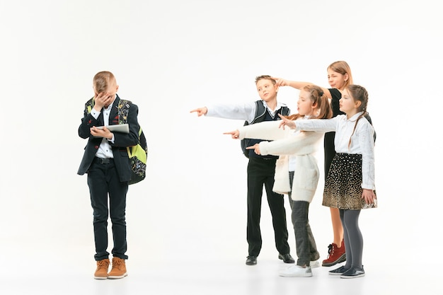 Little boy standing alone and suffering an act of bullying while children mocking