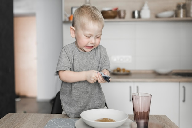Little boy standing on chair squeezing the packet in the bowl