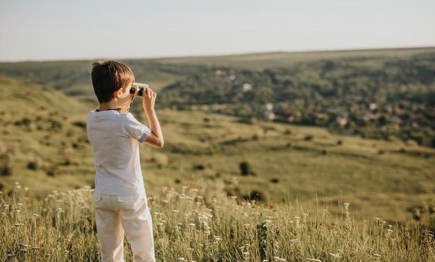 Little boy standing on green hill and looking through binoculars