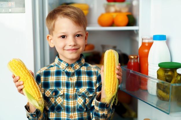 開いた冷蔵庫の前に立って食べ物を選ぶ小さな男の子