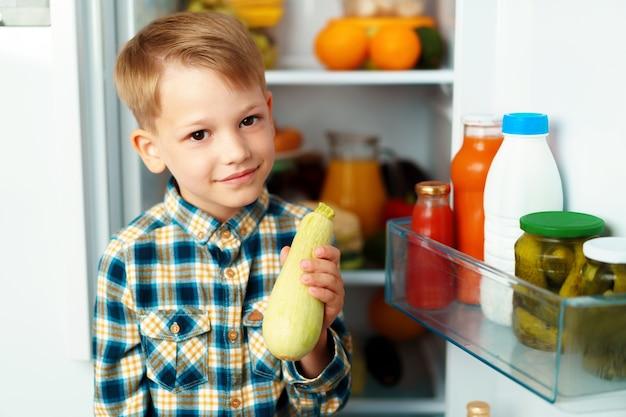 Маленький мальчик стоит перед открытым холодильником и выбирает еду
