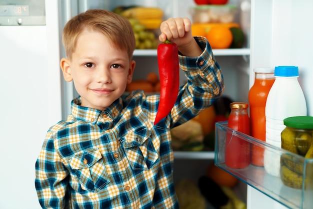 Маленький мальчик, стоящий перед открытым холодильником и выбирающий еду