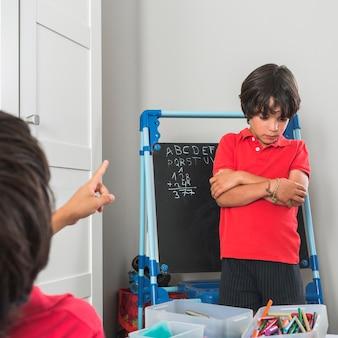 Little boy standing near blackboard ashamed