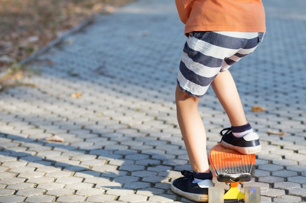 屋外でオレンジ色のスケートボードに立っている小さな男の子