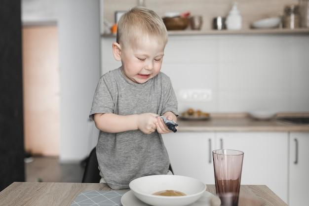 그릇에 패킷을 짜내는 의자에 서있는 어린 소년